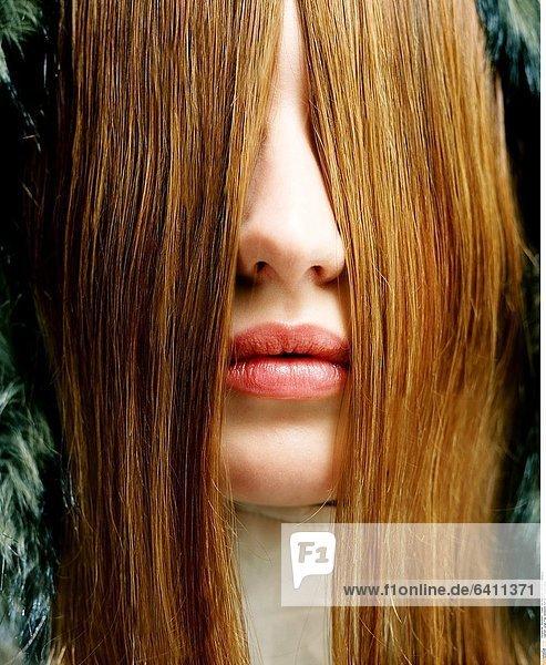 Junge Frau versteckt sich hinter ihren Haaren