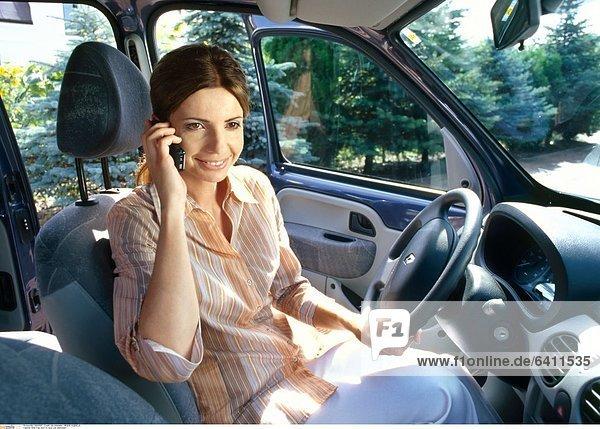 Eine Frau sitzt im Auto und telefoniert