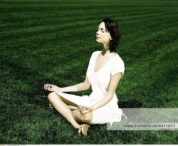 Junge Frau meditiert im Freien