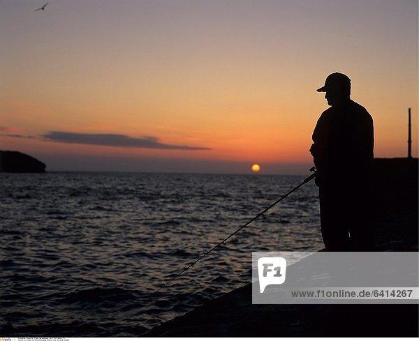 Ein Angler bei Sonnenuntergang  Mullion Cove  Cornwall  England