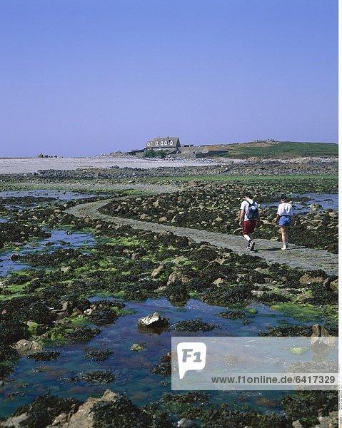 Urlauber wandern zur Lihou Insel  Guernsey