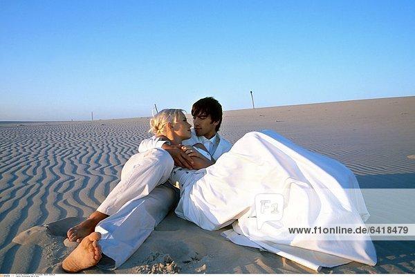 Hochzeitspaar liegt im Sand