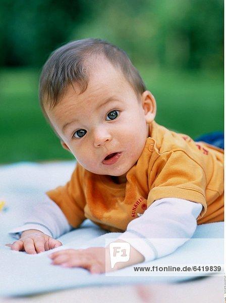 Ein Baby liegt auf einer Decke im Garten