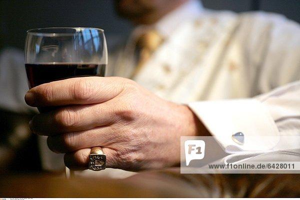 Ein älterer Mann trinkt Wein