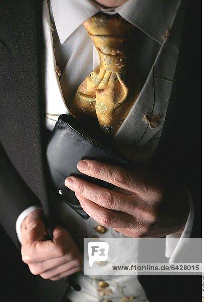 Ein edel gekleideter Mann steckt seine Geldbörse ein