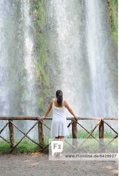 Eine junge Frau vor einem Wasserfall