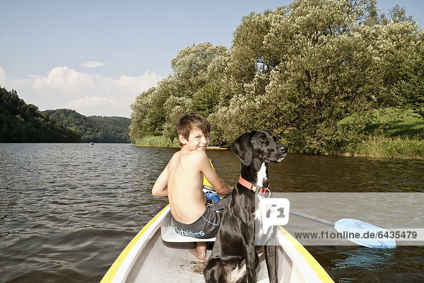 Boy paddling in a canoe  with his hunting dog  mongrel
