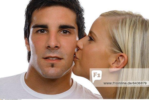 Eine junge Frau küsst einen jungen Mann auf die Wange