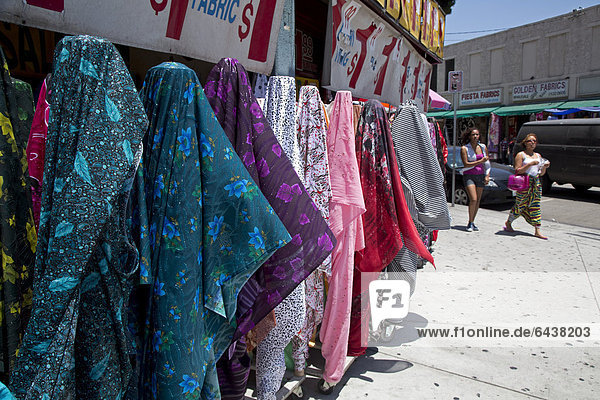 Clothing and fabric for sale on the sidewalk outside stores in the fashion district  Los Angeles  California  USA