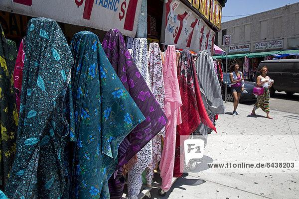 Kleidung und Stoffe zum Verkauf auf dem Bürgersteig vor Läden im Mode-Viertel von Los Angeles  Kalifornien  USA
