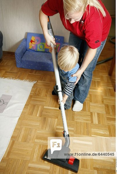 Kleiner Junge hilft seiner Mutter beim Staubsaugen