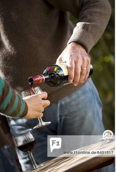 Ein Mann schenkt einer Frau ein Glas Wein ein.