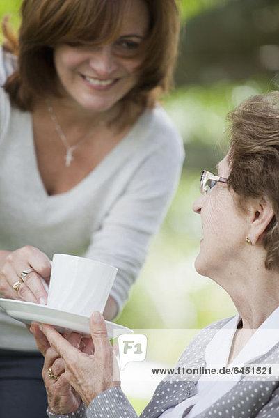 Eine Frau  die einer älteren Frau eine Tasse Tee gibt.