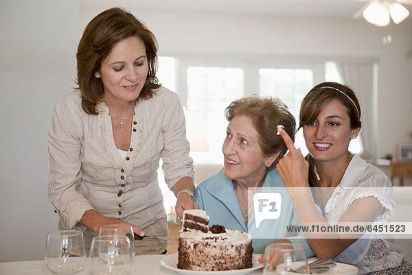 Eine Frau serviert Kuchen für ihre Mutter und Tochter.