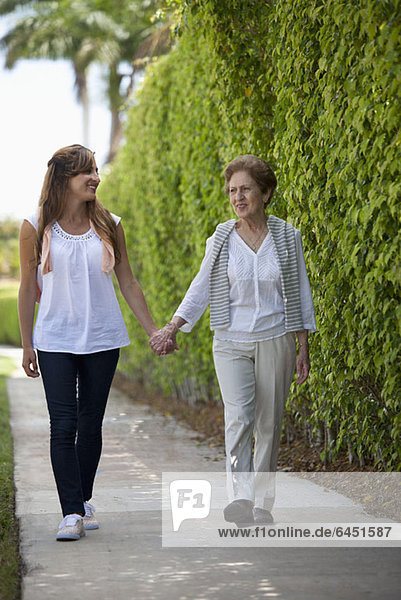 A senior woman and a young women holding hands and walking together