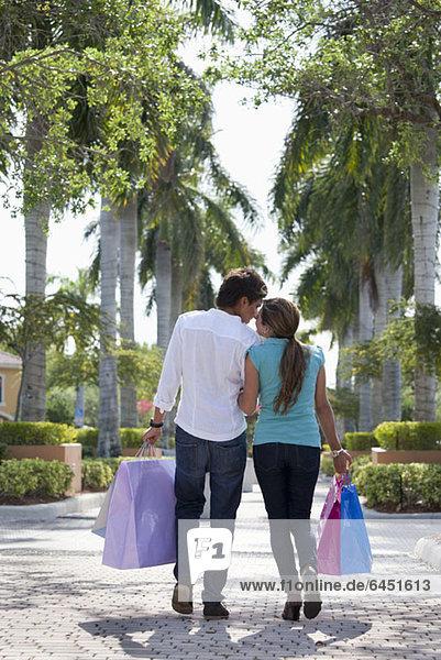 Ein junges Paar geht Arm in Arm und trägt Einkaufstaschen.