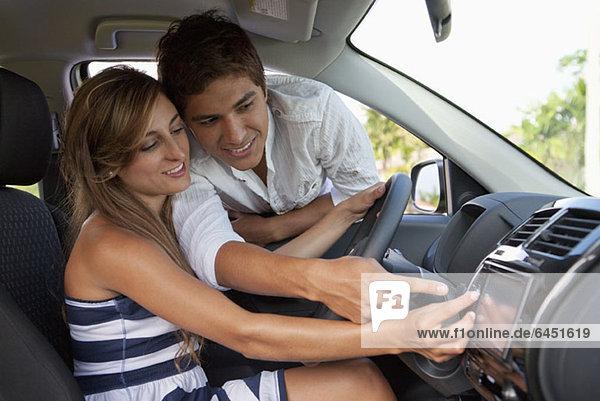 Ein Mann  der im Autofenster lehnt und seiner Freundin mit dem GPS hilft.