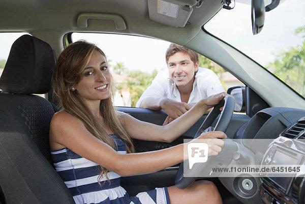 Ein Mann  der im Autofenster lehnt und die Freundin auf dem Fahrersitz anlächelt.