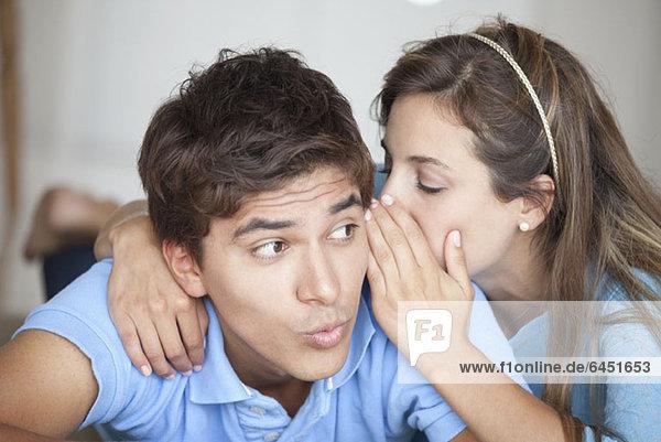 Ein Mann,  der überrascht sieht,  was seine Freundin ihm ins Ohr flüstert.