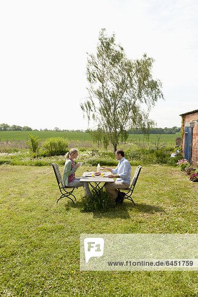 Ein Paar beim Frühstück im Garten Ein Paar beim Frühstück im Garten