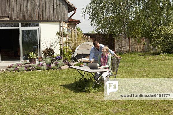 Eine Frau  die mit ihrem Freund lacht  während sie einen Laptop im Garten benutzt.