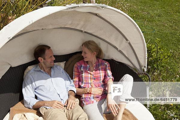 Ein Paar  das in einer Cabana im Garten liegt.