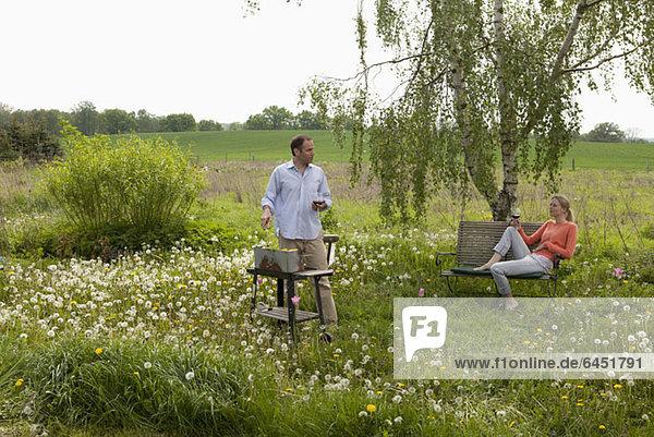 Ein Paar beim Grillen im Hinterhof  ländliche Umgebung