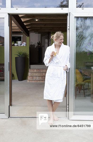 Eine glückliche Frau im Bademantel  die sich in die Tür ihres Hauses lehnt.