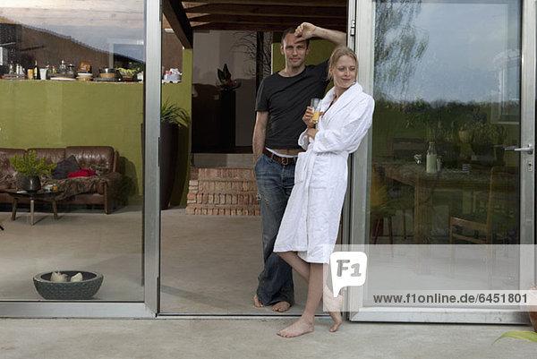 Ein Paar  das sich morgens gegen die Tür ihres Hauses lehnt.