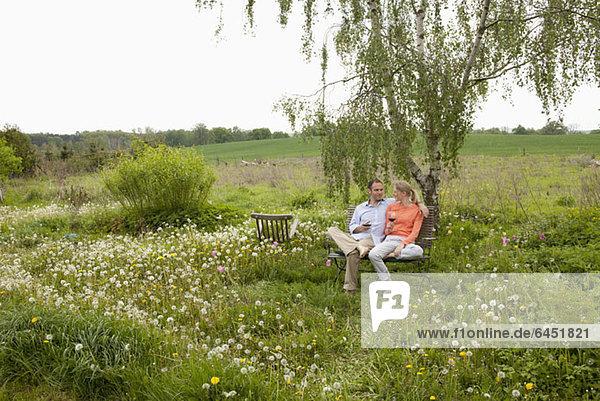Ein Paar spricht und genießt ein Glas Wein auf einer Bank im Garten.