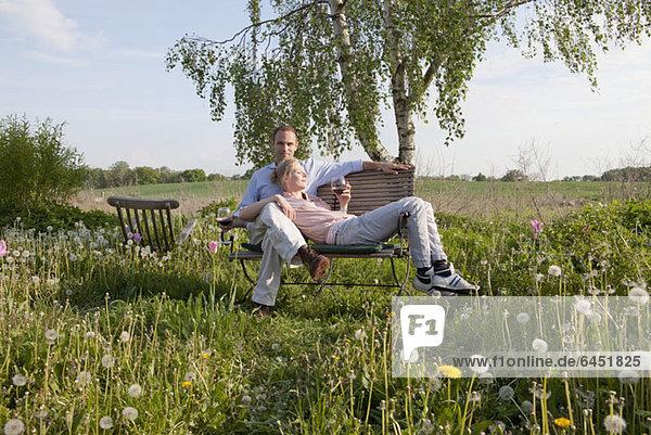 Ein Paar  das Sonne und Wein auf einer Bank im Garten genießt.
