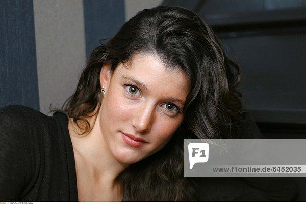 Eine junge Frau sitzt allein in einem Treppenhaus