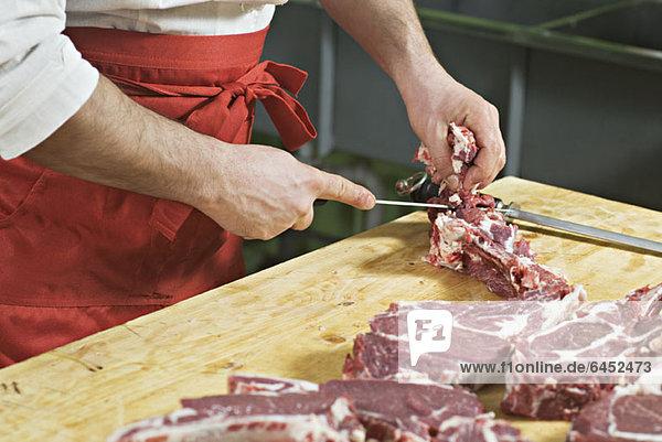 Detail eines Mannes beim Hacken von Fleisch