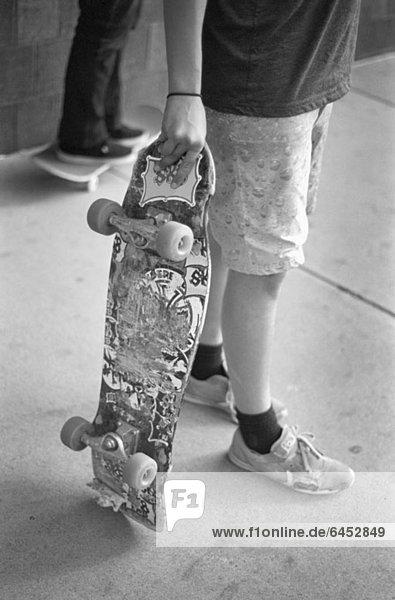 Ein Mann hält ein Skateboard  die Taille nach unten. Ein Mann hält ein Skateboard, die Taille nach unten.