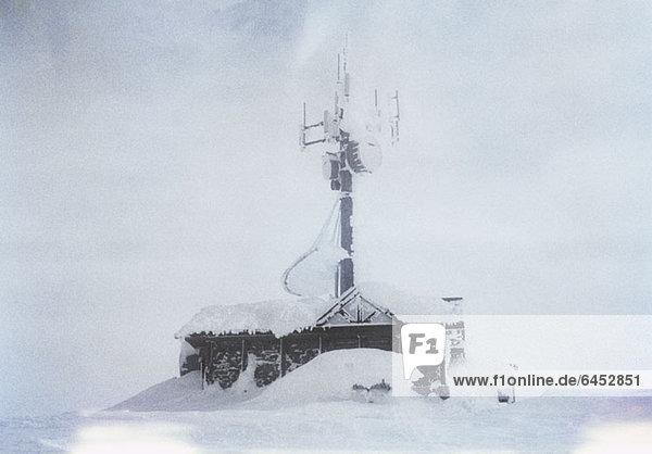 Ein Gebäude mit einer großen  schneebedeckten Antenne Ein Gebäude mit einer großen, schneebedeckten Antenne