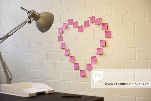 Herzförmig angeordnete Haftnotizen an einer Wand neben einem Schreibtisch