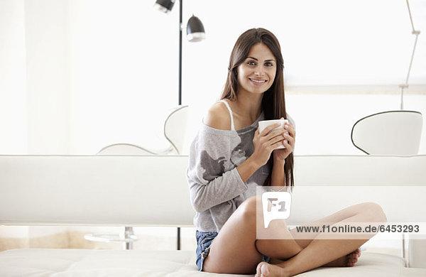 Frau mit gekreuzten Beinen hält Kaffeetasse