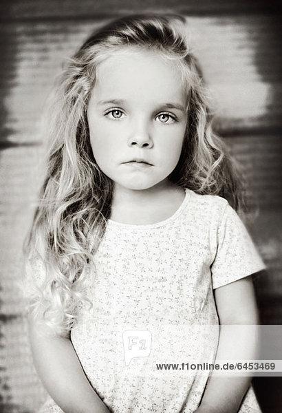Ein junges Mädchen schaut ernsthaft in die Kamera.