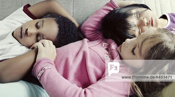 Drei Kinder  die gemütlich auf einem Sofa schlafen.