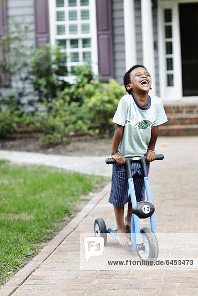 Ein sorgloser Junge lacht  während er auf einem Roller fährt.