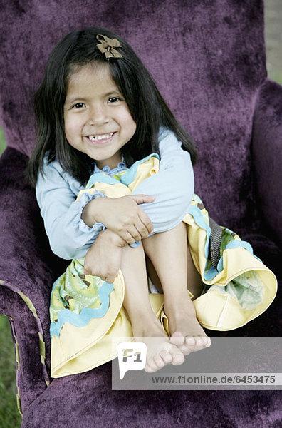 Ein junges lächelndes Mädchen sitzt in einem lila Sessel.