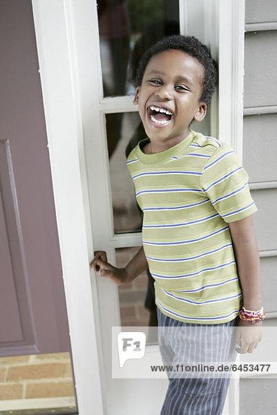 Ein fröhlicher  lachender Junge steht vor der Haustür seines Hauses.