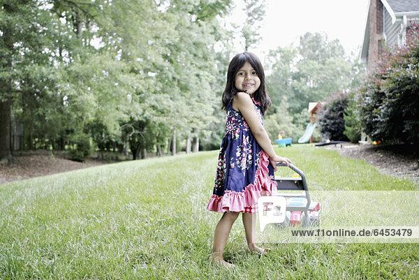 Ein junges Mädchen mit einem Spielzeug-Rasenmäher  der vorgibt  den Rasen zu mähen.