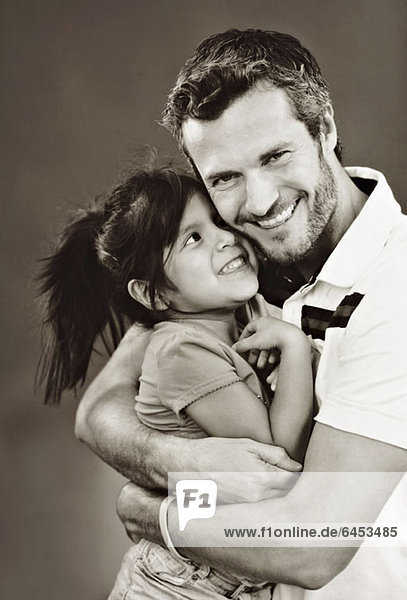 Ein Mann  der seine kleine Tochter umarmt.