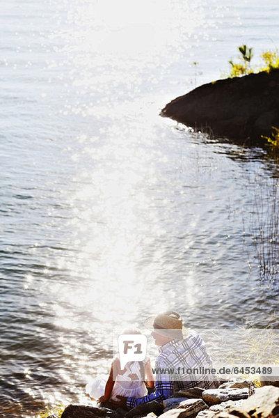 Ein Vater und seine Tochter genießen den Blick über den See