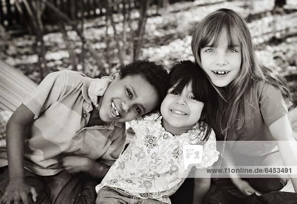 Drei fröhliche Kinder in einem Hinterhof