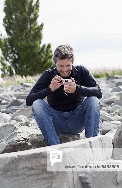 Ein Mann sitzt auf einem Felsen und lächelt etwas auf seinem Smartphone an.
