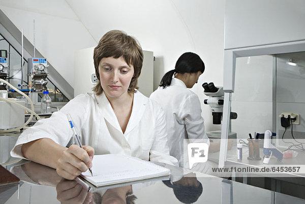 Ein Laborant schreibt Notizen  während ein anderer Techniker im Hintergrund arbeitet.