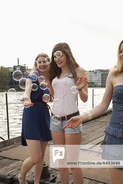 Drei Freundinnen beim Blick auf Blasen an der Spree  Berlin  Deutschland