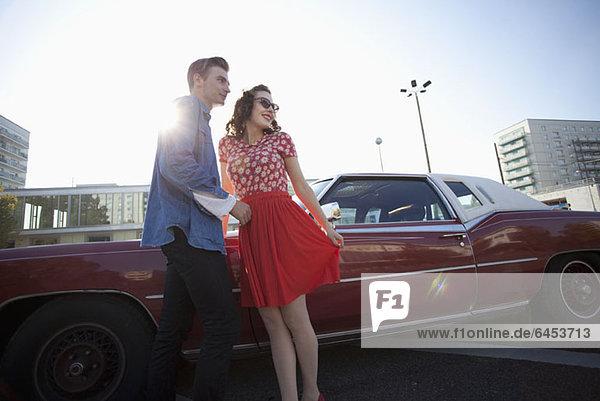 Ein fröhliches Rockabilly-Paar steht neben einem Oldtimer.